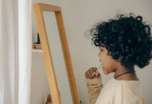 ethnic kid brushing teeth opposite mirror
